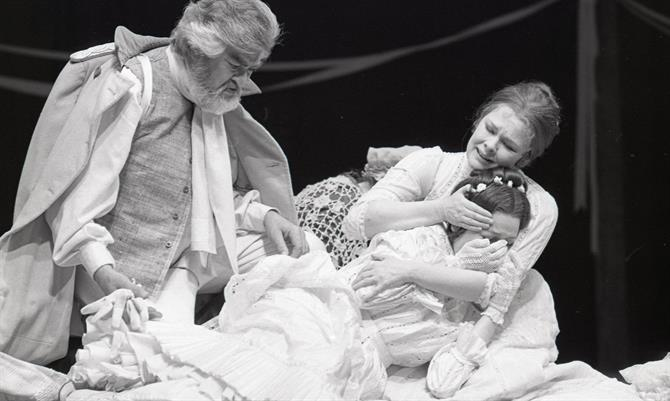 Leonato berates his daughter Hero as she lies on the ground supported by Beatrice