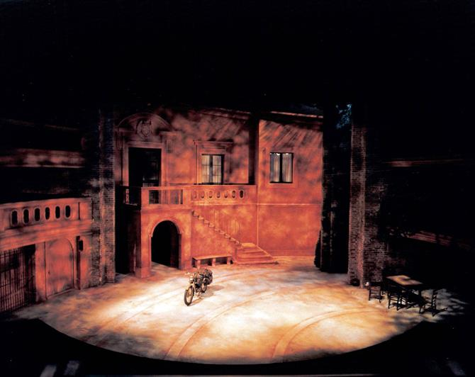 The Sicilian-style set for the play, with a motorcycle in front of a brick building