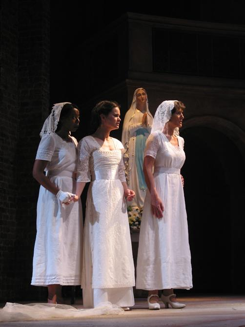 Three women in white bridal dresses stand in front of a statue of the Virgin Mary