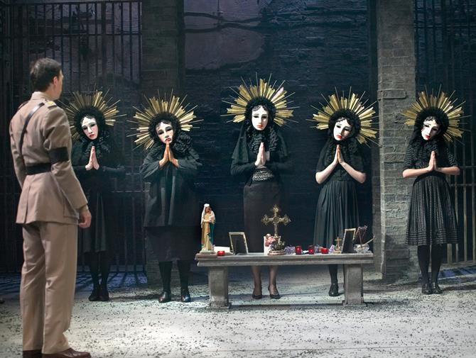 A soldier looks at a group of female mourners praying in Virgin Mary masks