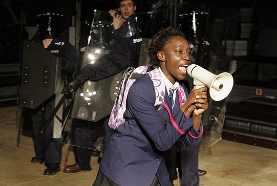 Sephy (Ony Uhiara) with a megaphone trying to persuade protesters to let nought pupils into Heathcroft School.