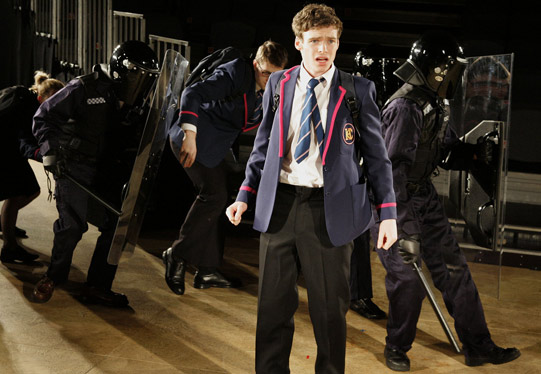 A boy in school uniform with armed riot police behind him