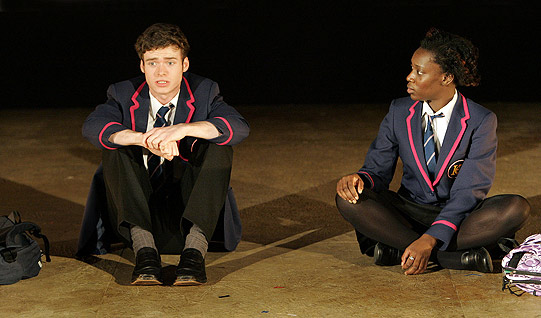 A boy and girl in school uniforms sit on the floor next to each other