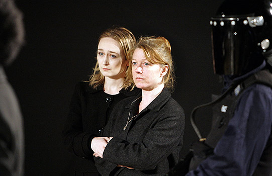 Two women in black hold on to each other