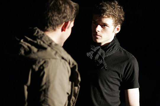 Two young men in dark clothes talk together