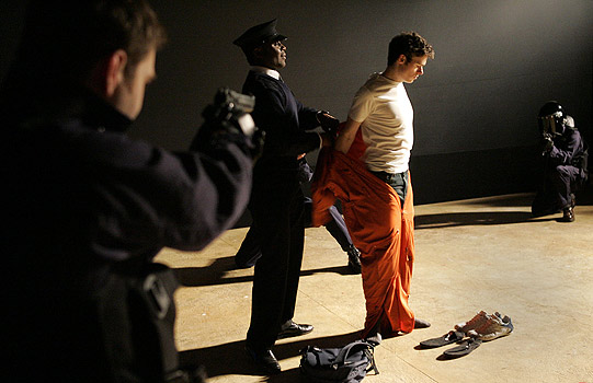 A gun is pointed at a man in an orange prison jumpsuit