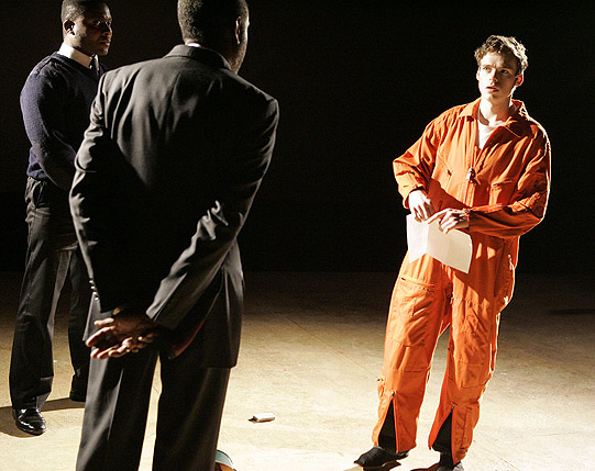 A boy in a prison uniform talks to a man in a suit as a police officer looks on