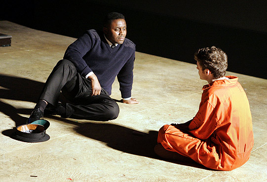 Callum in orange boiler suit waits for his execution with his guard