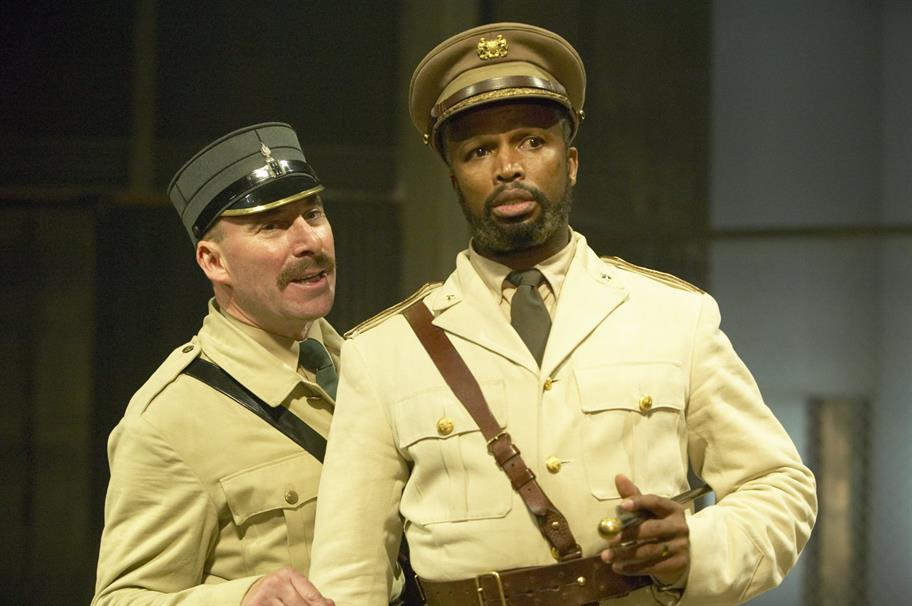 Iago  and Othello talk, both wearing military uniforms and caps