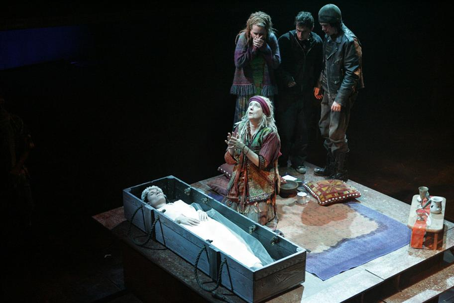 Thaisa lies in a coffin while a few people surround her, looking distressed