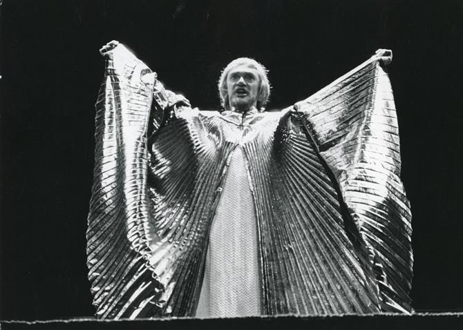 ichard Pasco as Richard II appears on a bridge over the stage wearing a large circular golden cloak