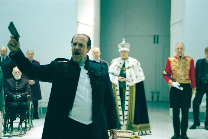 David Troughton surrounded by the minimalist white set and actors in royal dress