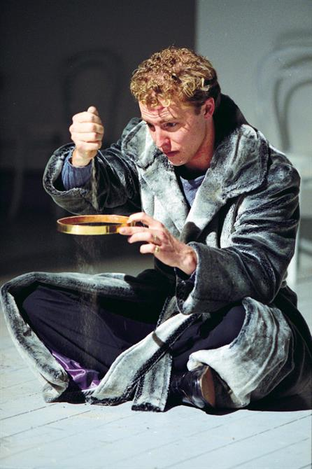 Samuel West sits on the floor, pouring sand through a golden band