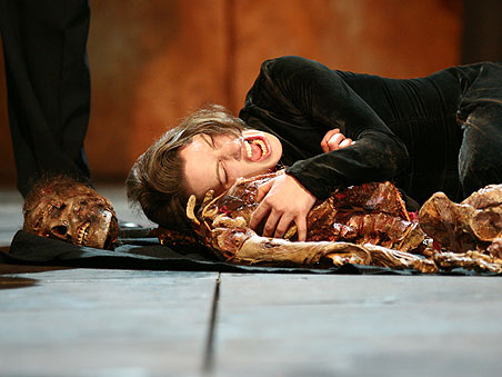 Woman lies on the stage floor next to a broken human skeleton