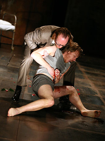 Two men on stage one lies on the floor bleeding