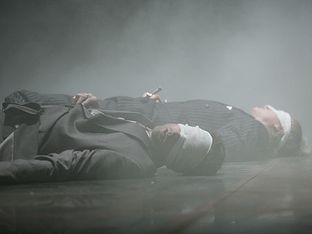 Two men lie on the stage floor, eyes covered