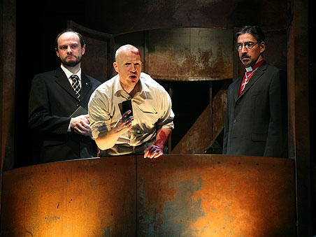 Two men in suits and another man covered in blood on stage