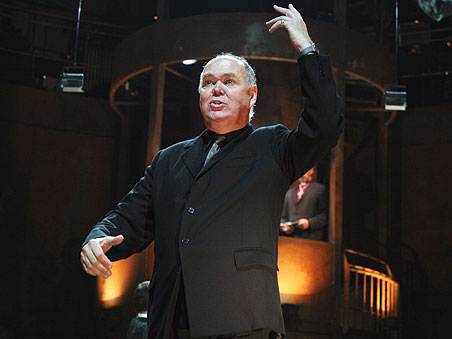 A man in a suit stands on stage with one hand raised upwards