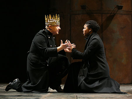 A man and woman sit kneel on the stage in deep discussion