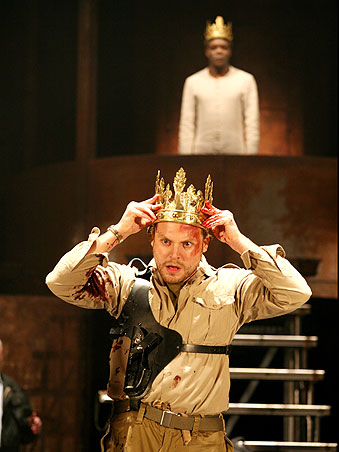 Richmond (Lex Shrapnel) places the crown on his head. The ghost of Henry VI (Chuk Iwuji) looks on.
