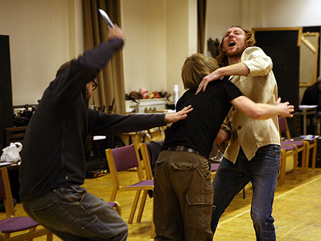 Three actors work on a fight scene in rehearsal