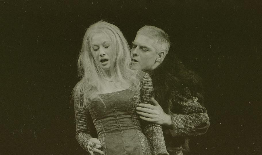Richard III, in a heavy coat and fur, wooing Lady Ann, a light-haired woman in a tight long dress