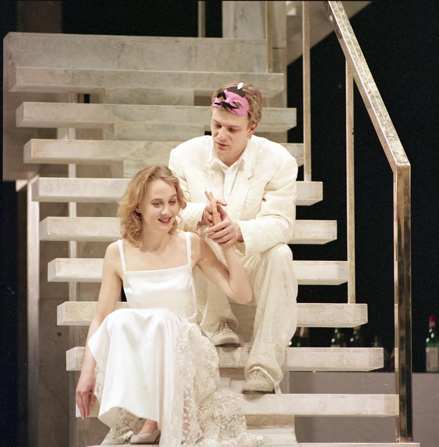 A young man holds the hand of a young woman as they sit on some steps