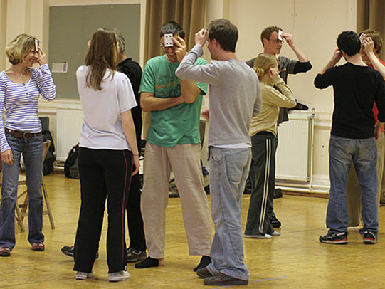 The cast rehearsing with a game to understand character interactions.