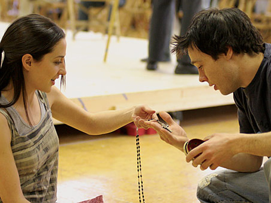 Morven Christie and Rupert Evans looking through available props such as rosary beads.