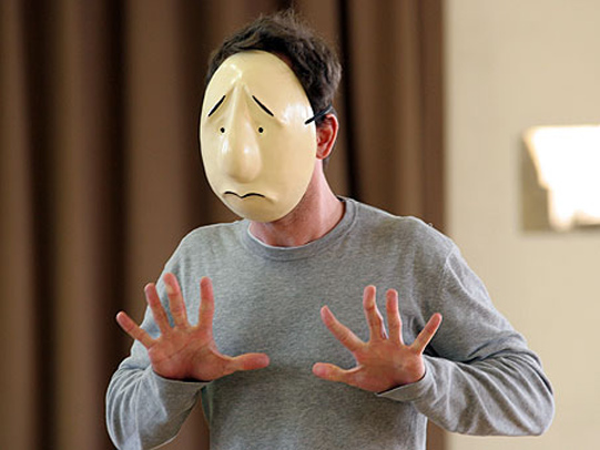 Jamie Ballard wearing a mask must communicate without speaking while being interviewed by the leader in rehearsal.