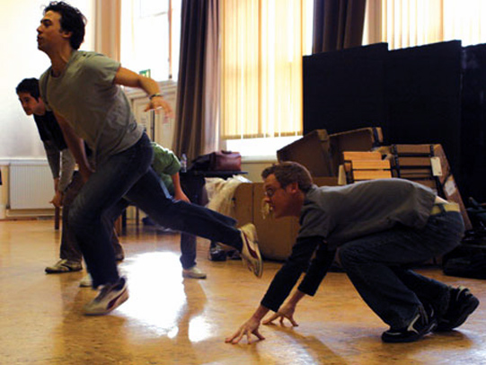 The cast in rehearsal playing a game to warm up in which they must steal a cloth in centre of the room.