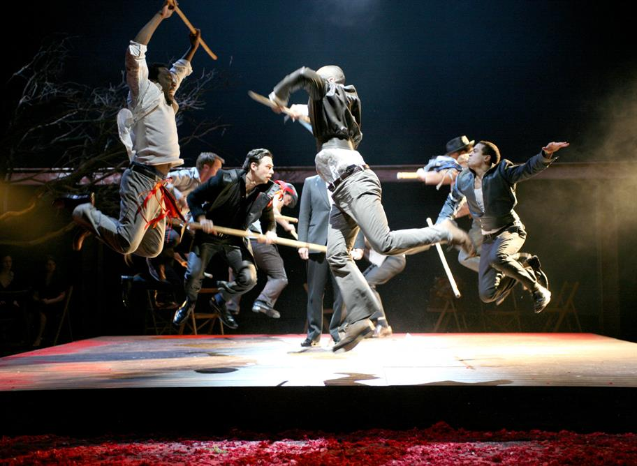 The Capulets and Montagues fight, jumping into the air as they brandish wooden sticks