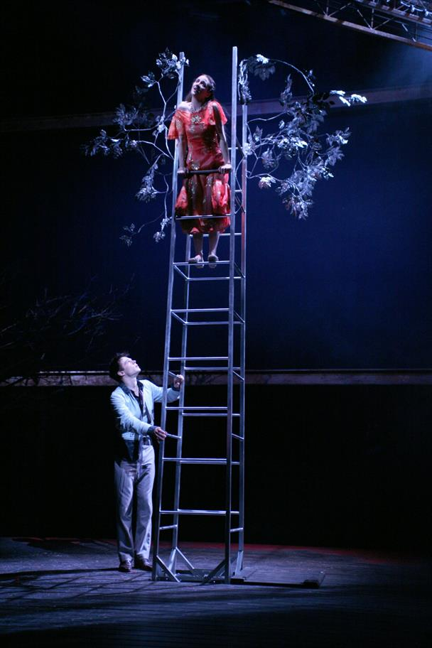 Juliet stands at the top of a ladder, supported by Romeo