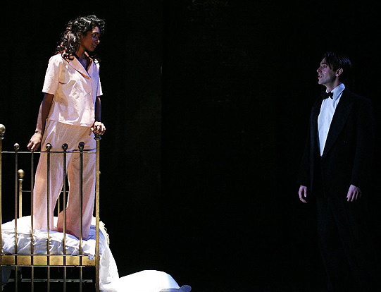 Romeo in a tuxedo talks to Juliet as she stands on a bed in her pink pyjamas