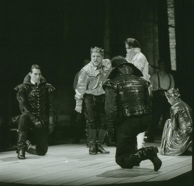 A black and white image of Edward II with the king dressed majestically centre stage, surrounded by kneeling subjects.