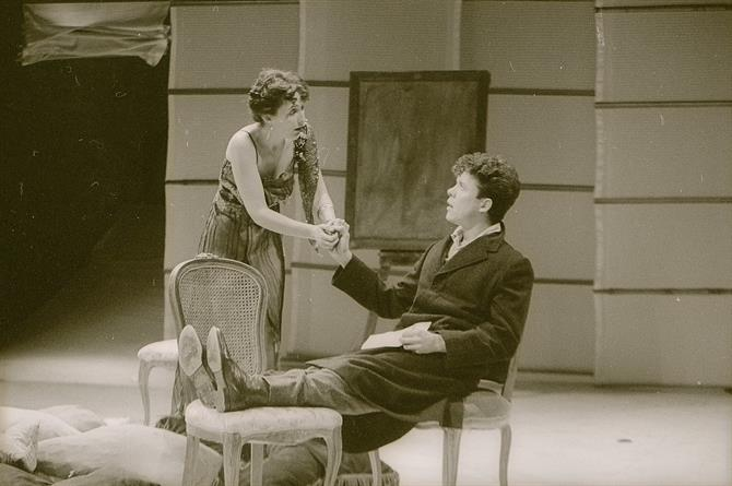 This image shows Alex Jennings in a suit portraying Fairfield, he is sitting on a seat conversing with a woman in a dress.