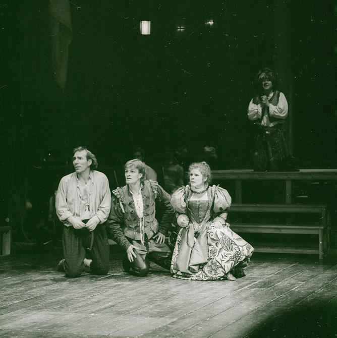 A black and white image of Sean Bean, Imelda Staunton and Pete Postlethwaite kneeling in the centre of the stage looking out into the distance.