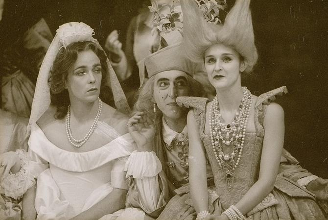 A black and white picture from The Silent Woman 1989 showing Epicoene (left) in a wedding dress, Sir Amorous La Foole (middle) dressed as a jester, and Madame Centaur (right) in a dress