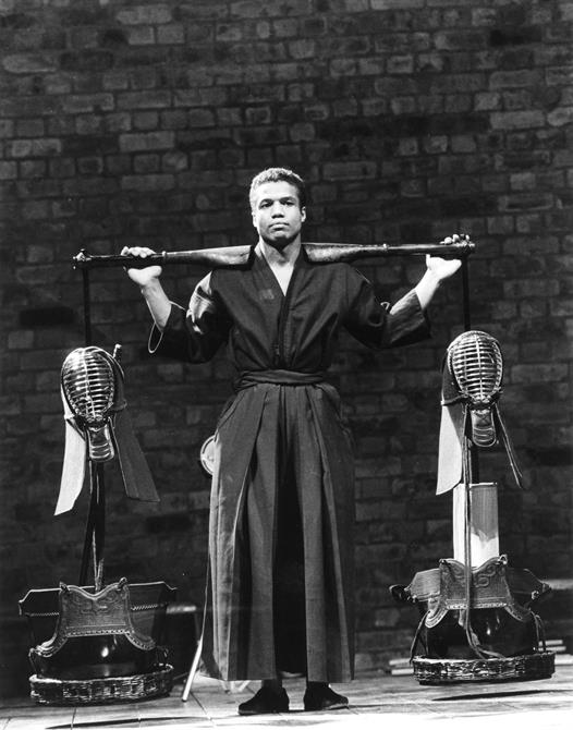 A black and white image of Hugh Quarshie carrying armour with a similar aesthetic to a fencing mask