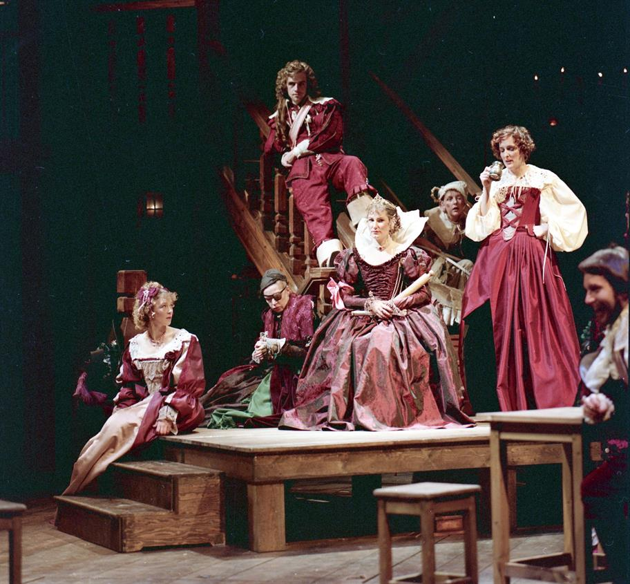 group of men and women seated on wooden staging in burgundy opulent dress. Gregory Doran is perched above them on a banister