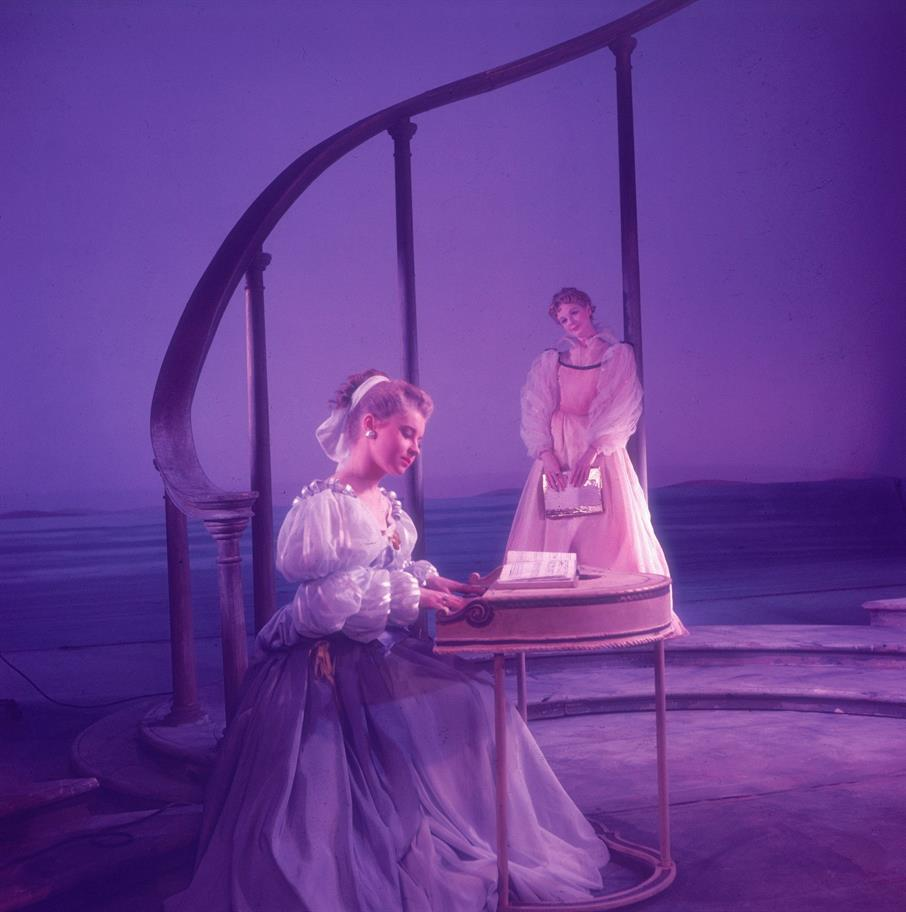 Portia in a puffy silk dress playing a harpsichord as Nerrisa looks on, also in a silk dress with puffy sleeves