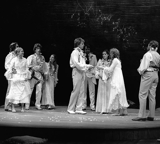 A wedding scene, the cast in relaxed white suits and ruffled dresses a contrast from the dark clothing from the trial scene.