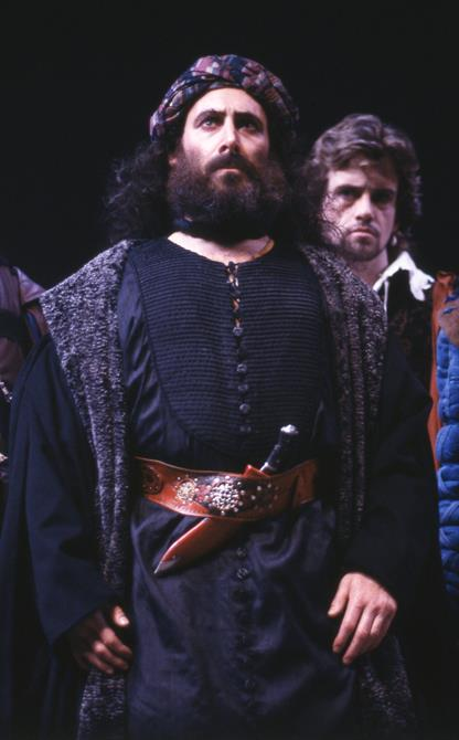 Solanio stands behind Shylock, who has a knife tucked into his waistband