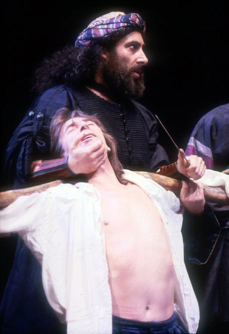 Shylock prepares to cut Antonio's flesh, holding a knife over his throat