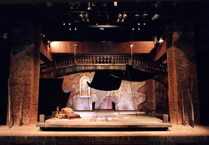 Kit Surrey's set for The Merchant of Venice, with a wooden balcony and crumbling plaster backdrop.