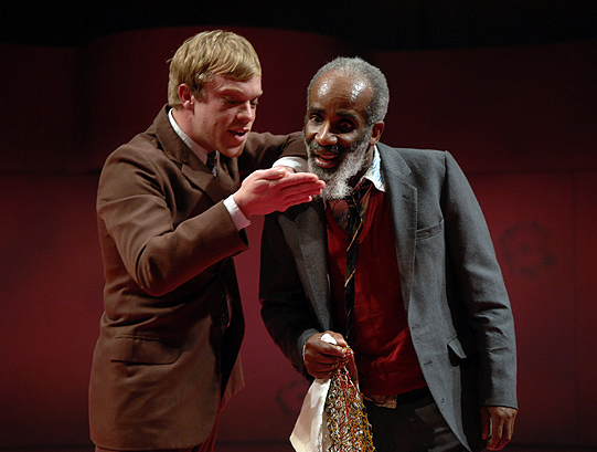 Production image of Launcelot (William Beck) playing a trick on Old Gobbo (Larrington Walker).