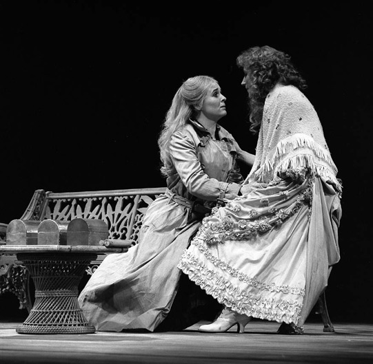 A woman kneels in front of another woman, whose hand is on her shoulder.