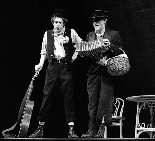 Two men, one with a guitar, another with an accordion.