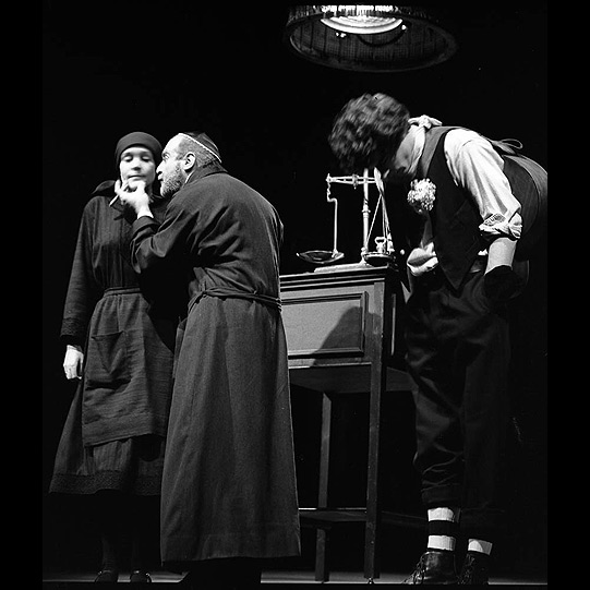 Shylock, in orthodox Jewish dress, talking to Jessica, as Launcelot Gobbo stands to the side.
