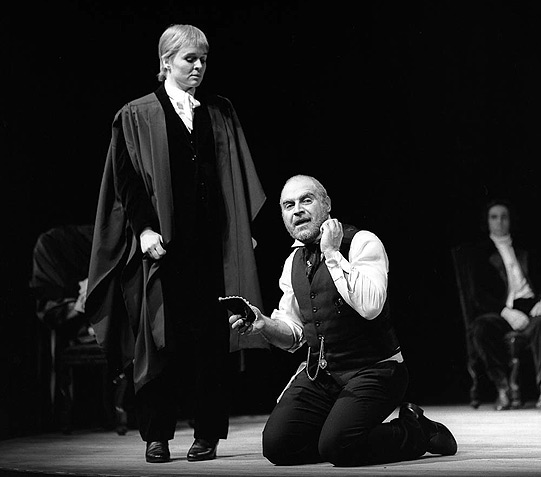 Portia stands over Shylock, signalling a power shift.
